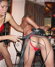 Asian lesbian strict Mistress has her female slave girl bent over to whip her naughty ass with a leather flogger